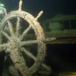 """Koło sterowe, obudowa kompasu i nadbudówka wraku trójmasztowego żaglowca """" Balder """", który zatonął w 1928 roku na głębokości 65 metrów. W tle Tomek. Alandy czerwiec 2006 roku."""